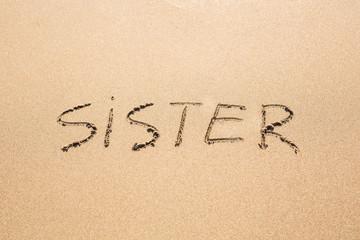 Sister word handwritten on a sand of beach