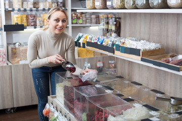 Positive woman selecting various candied fruits