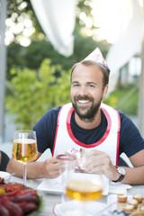 Portrait of smiling man at crayfish party, Stockholm, Sweden