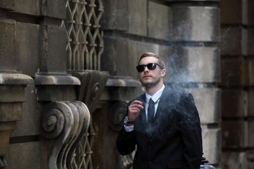 Handsome young man in black suit smoking small cigar on the street