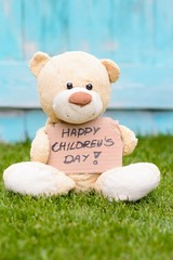 Teddy bear holding cardboard with information Happy Children's Day