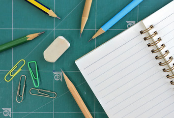 office, workspace concept and school accessories on the cutting mat background