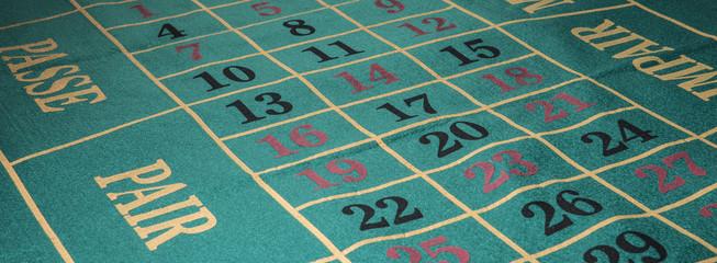 Dettagli scritte e numeri su tappeto da casinò verde.