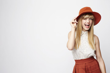 Blond woman with a wink wearing hat, studio