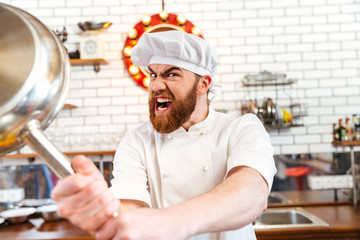 Crazy mad chef cook threatening with frying pan