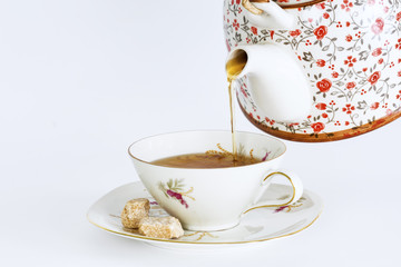 Teapot pouring tea into a cup of tea isolated on white background