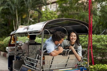 Smiling friends in rickshaw, Thailand
