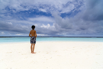 young boy sitting on exotic beach and watched the ocean