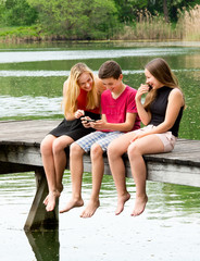 Drei Teenager haben draußen Spaß mit Smartphone