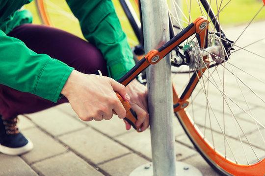 close up of man fastening bicycle lock on parking
