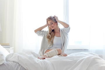 happy young woman stretching in bed at home