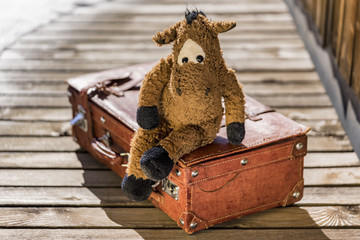 Single cute stuffed animal horse toy sitting in relaxed manner on suitcase over wooden deck outdoors