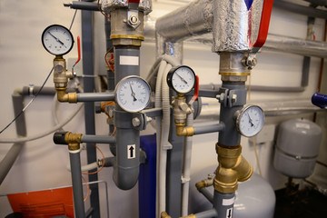 Close up of pipes, valves and manometer of heating system