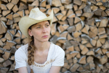 young girl in a cowboy hat on a background of wood