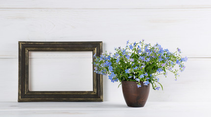 Me-nots flowers bouquet in clay vase and gilding photo frame on white wooden shabby board