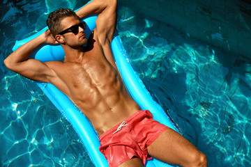 Man Summer Fashion. Beautiful Male With Sexy Body In Swimwear, Fashionable Sunglasses Tanning, Floating In Swimming Pool Water At Relax Spa Resort. Fitness Model With Skin Sun Tan Relaxing On Vacation