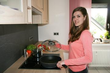 junge hübsche Frau beim Kochen