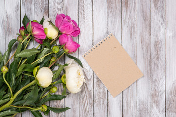 Notebook and bouquet of peonies flowers on wooden background. Place for text. Top view.