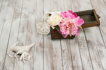 Beautiful flowers peonies in basket and decoration on light wooden background.