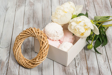 A box of marshmallows next to white peonies flowers on white wooden background.