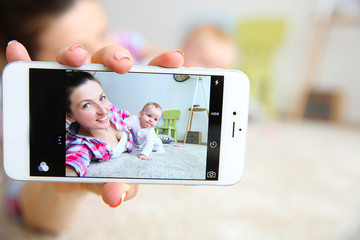 Young mother taking a selfie with her baby, close up