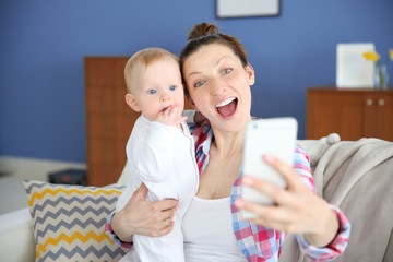 Young mother taking a selfie with her baby