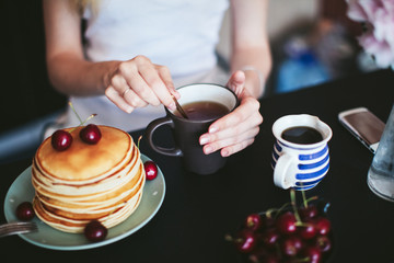 woman's hands holding a cup of tea. Breakfast of pancakes in the kitchen.