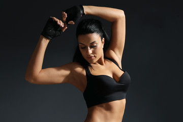 Attractive fitness woman on dark grey background