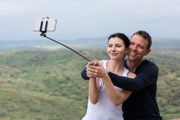 Junge Frau und Mann machen ein Selfie mit einem Selfie Stick während den Ferien und das Pärchen hat Spaß dabei