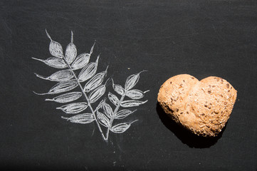 Heart shape of wholemeal bread with sunflowers seeds on blackboard background