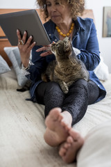 Woman with cat on bed holding digital tablet