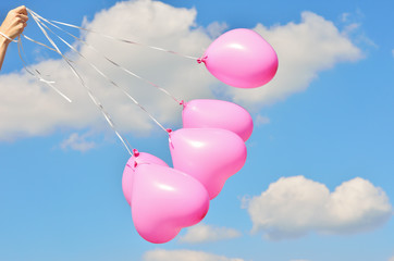 Pink balloons in a bunch on a white ribbons on a background of sky and clouds in a female hand