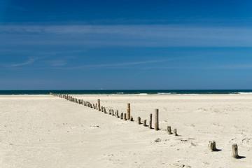 Canvas Prints Inspirational message Einsamer Strand mit Holzposten die bis zur Wasserkante führen