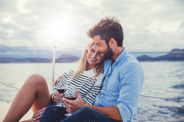 Young couple relaxing with red wine on yacht