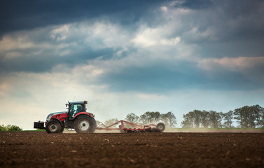 Farming tractor plowing and spraying on field Fototapete