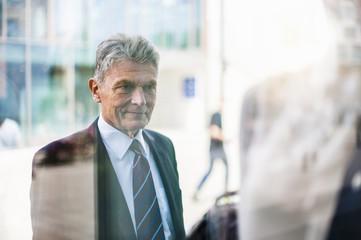 Senior man in suit looking at shop window