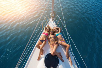 Girls lying on yacht. Smiling ladies wearing swimsuits. Have a happy summer. Today's weather is wonderful.