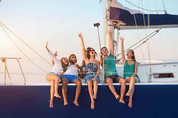 Cheerful people with selfie stick. Men with women on yacht. Remember this moment. Happiness that comes from heart.