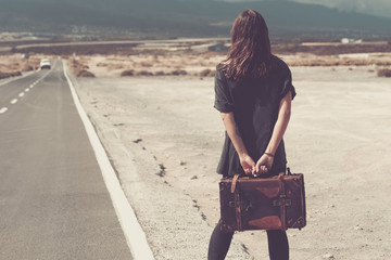 Young woman with suitcase walking on a road