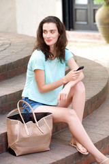Beautiful young woman sitting outside with mobile phone