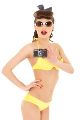 Girl in bikini with retro camera.
