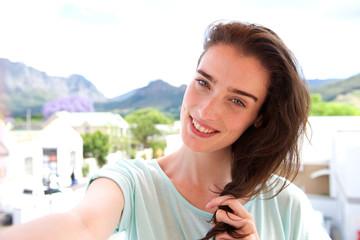 Happy woman taking selfie outdoors