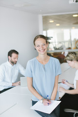 Portrait of smiling woman sitting with colleagues in office