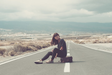 Young woman with suitcase sitting on the road