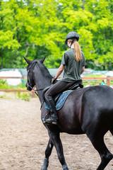 girl sportsman rides on horse