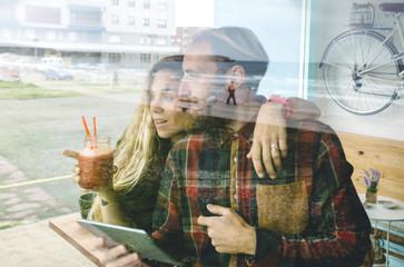 Couple having breakfast at cafe, using digital tablet