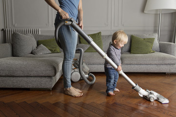 Laughing toddler helping his mother hoovering wooden floor Wall mural