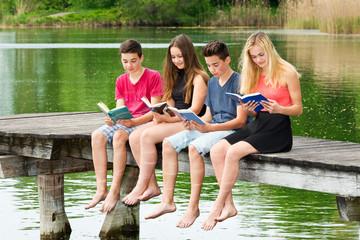 Gruppe Jugendliche lesen draußen ein Buch / Bücher