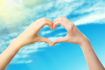 Female hands in shape of heart, on blue sky background