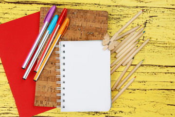 Office set with notebooks, colored pencils and pens on yellow wooden background